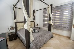 Interior design of bedroom in luxury holiday villa. Interior design decor furnishing of luxury show home holiday villa bedroom with four poster bed royalty free stock image