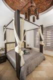 Interior design of bedroom in luxury holiday villa. Interior design decor furnishing of luxury show home holiday villa bedroom with four poster bed royalty free stock photo