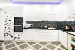 Interior design clean modern white kitchen with painted doors stock image