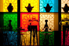 Interior design with colorful decorative glass bottles. And vases on the background of multicolored panels in vintage style Stock Photography