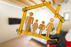 Interior Design Concept - Ruler with Family. Interior Design Concept - Hand with work glove holding a wooden meter ruler in the shape of house with symbol of a Stock Photo