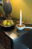 Interior design detail. Still life of home interior detail decorated with candles and fruit basket Royalty Free Stock Images