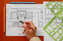 Interior design drawings. Designer's hand with pencil and new kitchen design drawings Royalty Free Stock Image