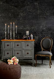 Interior design with dresser. Gray drawer, and gray chair on stucco wall, in romantic atmosphere Stock Photos