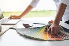 Interior design or graphic designer working on project of archit. Ecture drawing with work tools and color swatches, colour chart in digital tablet at workplace Royalty Free Stock Images