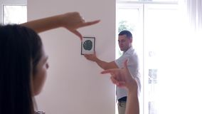 Interior Design, handsome male hangs painting while girl makes frame with finger and decide on decoration on walls. At apartment stock video footage