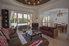 Interior design of luxury villa living room. Living room lounge area in luxury villa show home showing interior design decor furnishing and garden view Royalty Free Stock Photo
