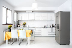 Interior design, modern and minimalist kitchen with appliances and table. Open space in living room, minimalist decor