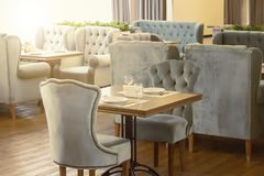 The interior design of the restaurant and a table with wine glasses for two in daylight. The interior design of the restaurant and a table with wine glasses for stock photography