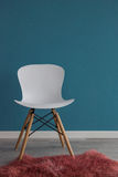 Interior design scene with a modern white chair on blue wall. Interior design scene with a modern white chair and pink rug Royalty Free Stock Photo