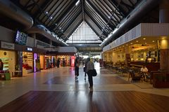 Interior design of Siem Reap Angkor International Airport with shops and restaurant. This image is taken at the waiting area with plenty of red chairs nearby the royalty free stock photo