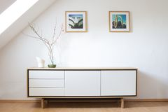 Modern sideboard in bright living room. Interior design: Wooden, white sideboard in modern loft Stock Photos