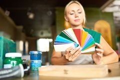 Interior Designer Choosing Color Palette. Portrait of beautiful blonde woman holding color swatches choosing palette for art and craft project in workshop, focus royalty free stock photography