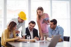 Interior designer with colleagues discussing blueprint Royalty Free Stock Images