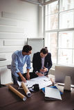Interior designer with coworker looking at blueprint Royalty Free Stock Photos