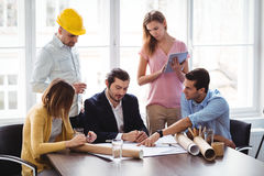 Interior designer with coworkers discussing blueprint Royalty Free Stock Photos