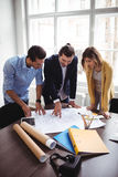 Interior designer with coworkers looking at blueprint Royalty Free Stock Image