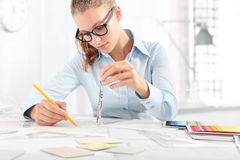 Interior designer draws at desk in office, with pencil and compa Royalty Free Stock Photography
