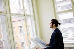 Interior designer holding blueprint while looking through window Stock Photos