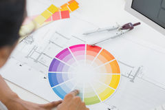 Interior designer looking at colour wheel at desk stock photo