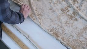 Interior designer measuring a length of neutral colored fabric. Close up. Slow motion. Professional shot in HD resolution. 109. You can use it e.g. in your stock footage