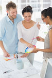 Interior designer showing colour wheel to smiling clients Royalty Free Stock Images