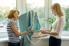 Interior designer shows samples of fabrics and accessories for curtains in new house. Interior designer shows samples of fabrics and accessories for curtains in stock image