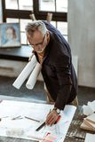 Interior designer using rulers and pencils finishing sketches. Finishing sketches. Grey-haired interior designer using rulers and pencils while finishing stock images