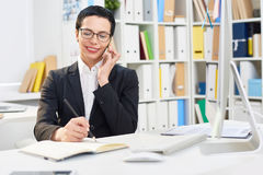 Interior Designer at Work. Attractive middle-aged designer writing down order details while talking to her client on mobile phone, interior of modern office on stock photography