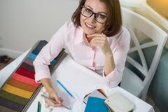 Interior designer, at the workplace with samples of fabrics and accessories for curtains and upholstery. Stock Photography
