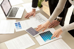 Interior designers teamwork with pantone swatch and building pla. Close up view of Interior designers teamwork with pantone swatch and house building plans on stock photo