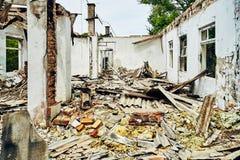 Interior destruído do salão da fábrica com uma grande massa de telhas dos restos e de telhado, sem teto, telhado e janelas imagem de stock royalty free