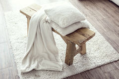 Interior details. Still life details, stack of white cushions and blanket on rustic bench on white carpet Royalty Free Stock Images