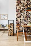 Interior with dining area. Firewood holder and wooden log wallpaper in spacious interior with open living room and separated dining area Stock Image
