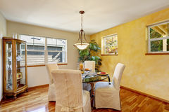 Interior of dining room with yellow wall and hardwood floor. Stock Images