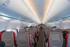 Interior do avião com os passageiros em assentos e em comissária de bordo dentro imagem de stock royalty free