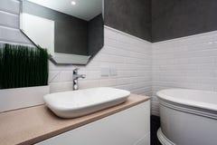 Interior do banheiro Banheiro brilhante com telhas novas Bacia nova, dissipador branco e grande espelho imagens de stock royalty free