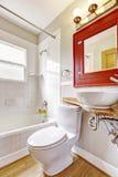Interior do banheiro com armário vermelho e o dissipador branco da embarcação Imagem de Stock