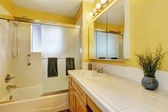 Interior do banheiro em tons amarelos e na parte superior contrária da telha Foto de Stock