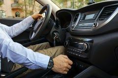 Interior do carro com o motorista masculino que senta-se atrás da roda, luz macia do por do sol Painel luxuoso e eletrônica do ve fotos de stock