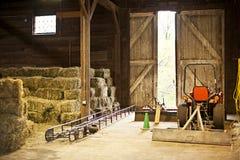 Interior do celeiro com balas de feno e equipamento de exploração agrícola Fotos de Stock