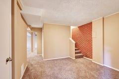 Interior do corredor do porão com assoalho de tapete e parede de tijolo Foto de Stock Royalty Free