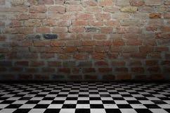 Interior do fundo da xadrez em uma sala escura e em uma parede de tijolo Fotografia de Stock Royalty Free