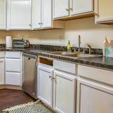 Interior do quadrado de uma cozinha com armários brancos e os contadores construídos contra a parede fotos de stock royalty free
