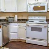 Interior do quadrado de uma cozinha com armários brancos e os contadores construídos contra a parede fotos de stock