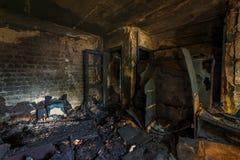Interior do queimado pelo apartamento em um prédio de apartamentos, mobília queimada do fogo fotografia de stock