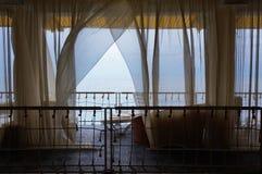 Interior do restaurante de Seaview Terraço ou varanda branca com as cabines separadas sob a barraca e as cortinas brancas Fotografia de Stock Royalty Free