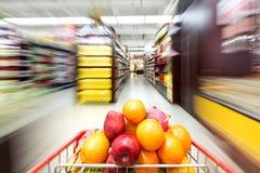 Interior do supermercado, enchido com o fruto do carrinho de compras Imagem de Stock
