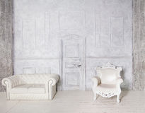 Interior do vintage com sofá, poltrona, parede do estuque e porta Foto de Stock Royalty Free