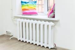 Interior doméstico da sala com o radiador do aquecimento central sob a janela Fotos de Stock Royalty Free